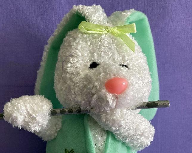 Plush Easter Bunny Flutist made of white chenille and wearing a green vest decorated with carrots. Playing a silver wood flute. Makes a great basket stuffers, special gift for that special flutist in your life, or  gift the collector who loves plush collectibles.