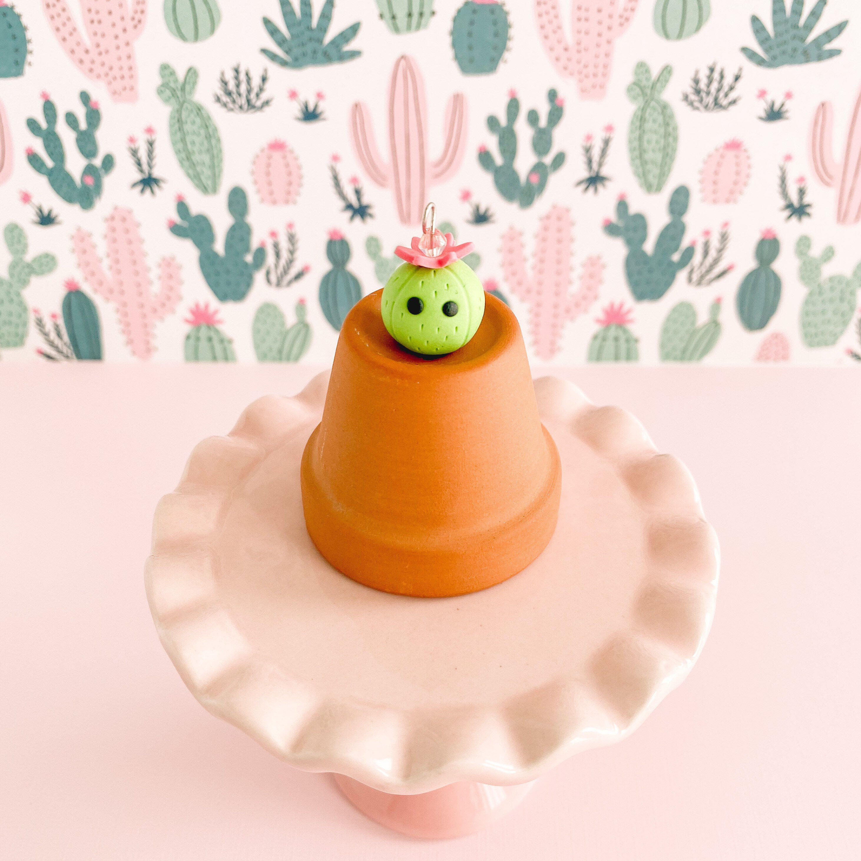 fireflyFrippery Cute Cactus Charm with Flower on top of Miniature Terra Cotta Pot on Pink Display