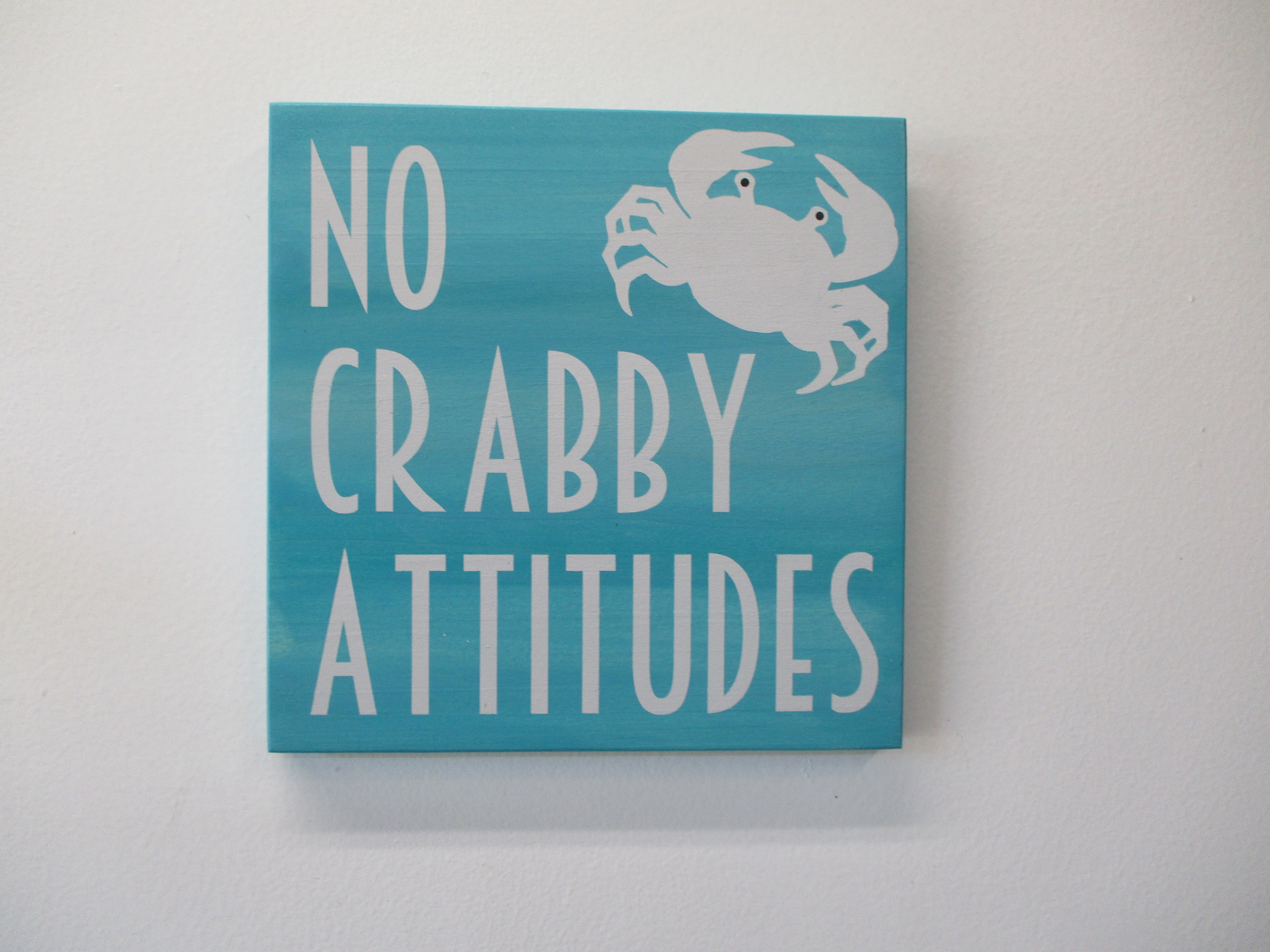No Crabby Attitudes Wooden Beach Sign.  Fun sign to put a smile on everyone's face.  Measures approximately 8 inches x 8 inches ready to hang. Painted in Calypso and blended with a soft Bahama green for depth.