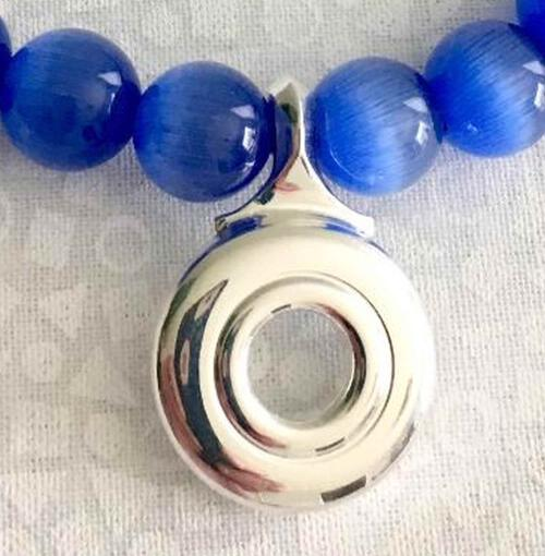 Close up of blue glass beads, shilver open hole flute key pendant.
