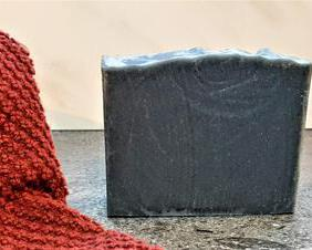 a picture of a bar of medium gray soap with a red towel in the foreground